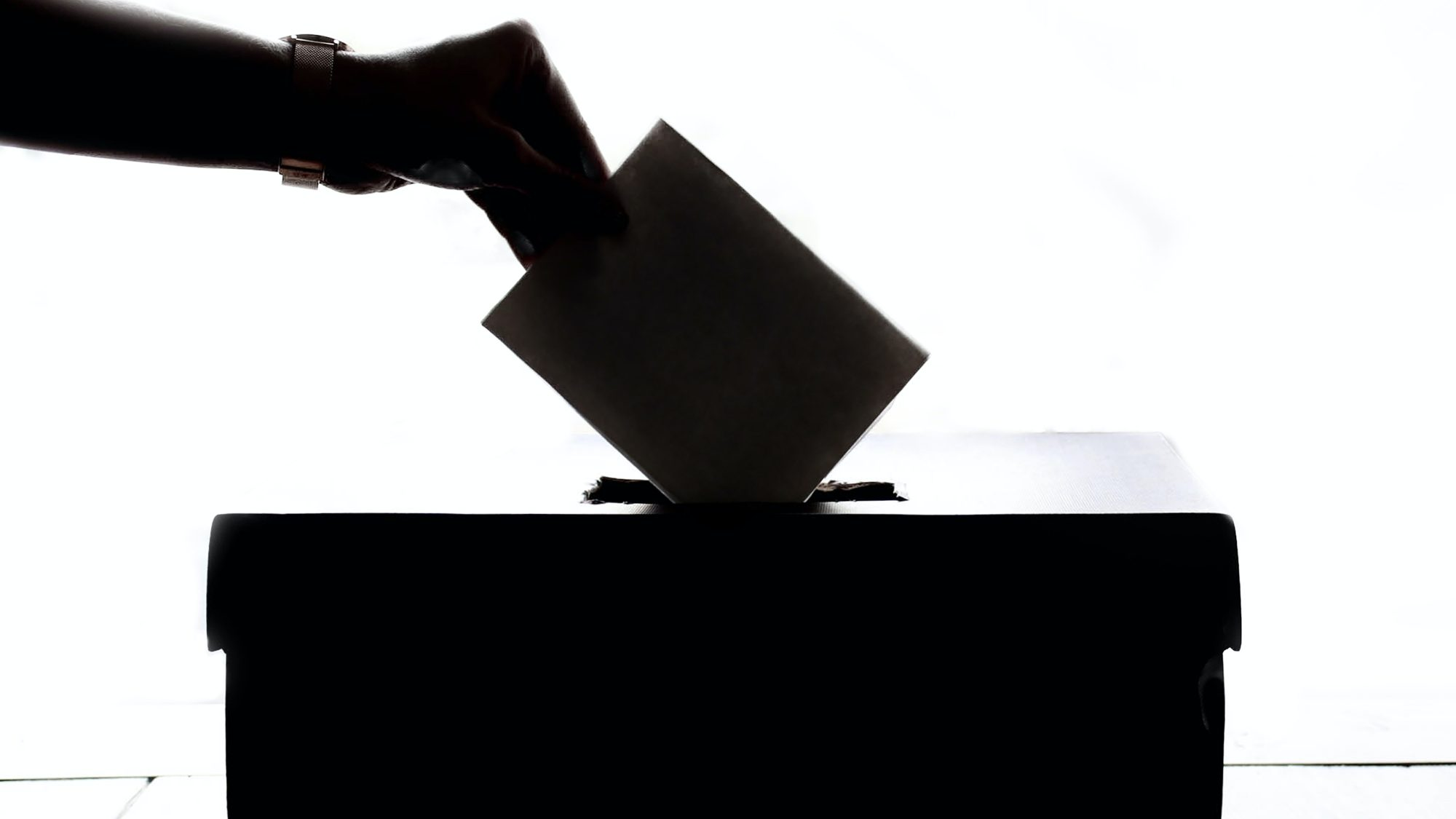 Woman places envelope in ballot box