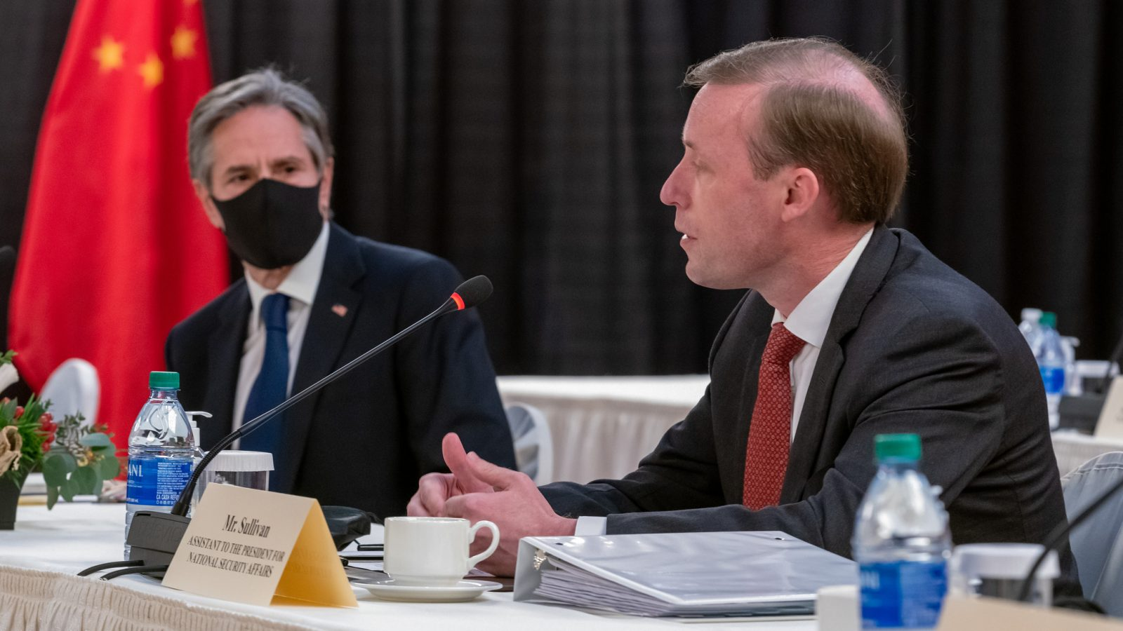 Secretary Blinken and NSA Sullivan sit in front of a Chinese flag during negotiations in Alaska