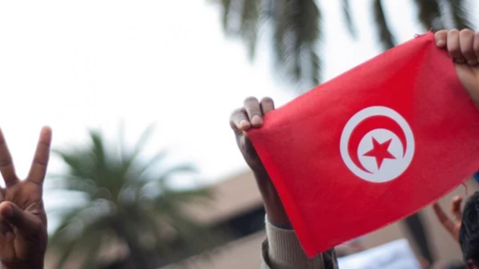 Citizens raise the peace sign and the Tunisian flag