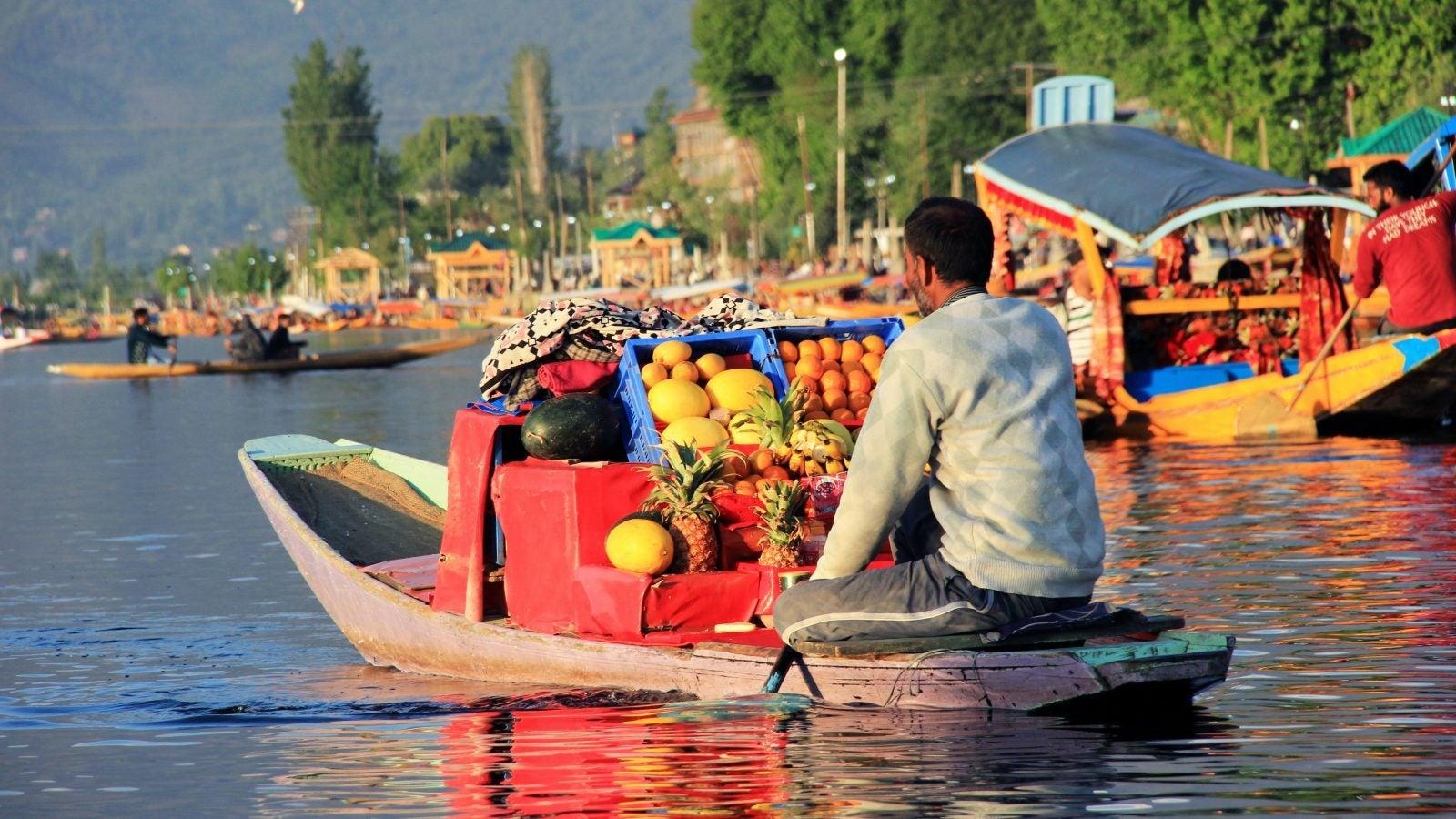 Man delivers fruit on a boat in Kashmir
